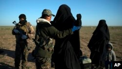FILE - A woman is frisked by a U.S.-backed Syrian Democratic Forces (SDF) fighter at a screening area after being evacuated out of territory held by Islamic State group militants, in the desert outside Baghuz, Syria, March 1, 2019.