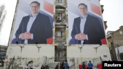 FILE - People pass posters of Serbian Prime Minister Aleksandar Vucic in Novi Sad, Serbia, March 18, 2017.