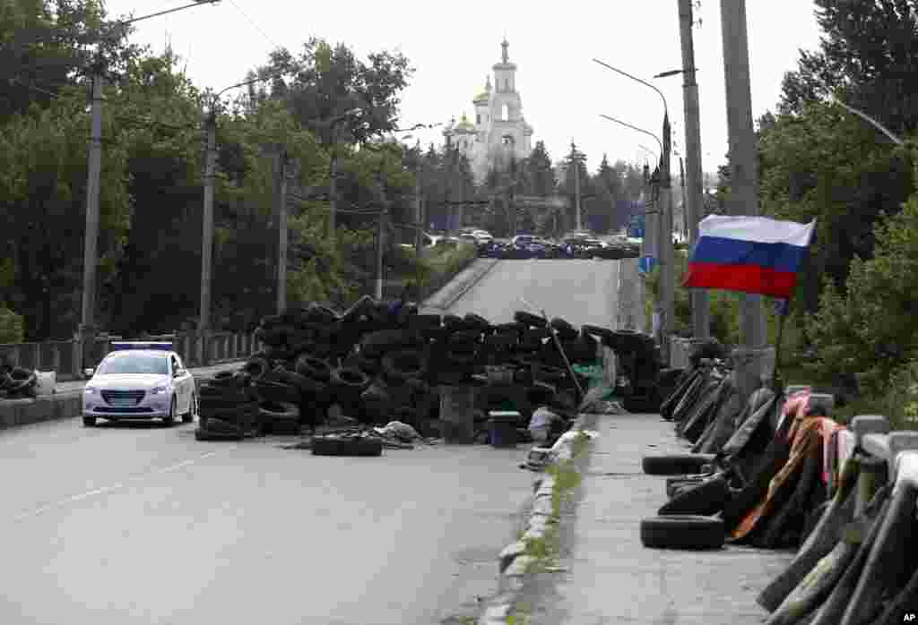 A car passes by the barricades with a Russian national flag on a road leading into Slovyansk, eastern Ukraine, May 13, 2014.
