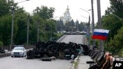 5月13日一辆轿车通过乌克兰东部一个悬挂俄罗斯国旗的路障