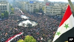 In this handout photograph released by Syria's national news agency SANA, supporters of Syria's President Bashar al-Assad attend a rally at al-Sabaa Bahrat square in Damascus, Syria, November 28, 2011.