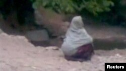 A woman accused of adultery squats in front of a crowd before her public execution by a man who Afghan officials say is a member of the Taliban, in a village outside Kabul in this still image taken from undated footage released July 7, 2012.