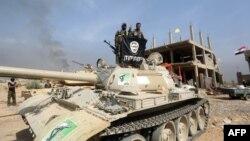 지난 19일 이라크 바그다드 북부 지역에서 이슬람 수니파 무장조직 ISIL 대항 전투에 투입된 이라크 시아파 민병대가 ISIL 깃발을 거꾸로 들고 있다.