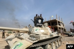 FILE - Iraqi Shiite fighters from the Popular Mobilisation units, fighting alongside Iraqi government forces, display, upside down, the flag of the Islamic State (IS) group during a military operation aimed at the centre of Baiji, Iraq, Oct. 19, 2015.