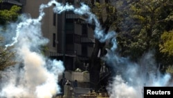 FILE - Anti-government protesters walk through tear gas during riots in Caracas, Apr. 6, 2014.