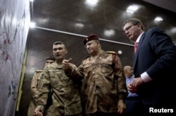 U.S. Defense Secretary Ash Carter, right, and Iraqi Lt. Gen. Abdul Amir al-Lami, center, look over diagrams and maps at the Combined Joint Operations Center in Baghdad, Iraq, July 23, 2015.