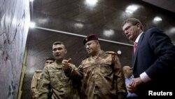 Menhan AS Ash Carter, (kanan) dan Letjen Abdul Amir al-Lami (tengah) mengamati diagram dan peta di Pusat Operasi Bersama Militer AS-Irak di Baghdad (23/7).