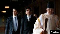 PM Jepang Shinzo Abe dipimpin pendeta Shinto ketika mengunjungi makam Yasukuni di Tokyo 26 Desember 2013.