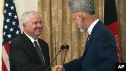 ທ່ານ Robert Gates ລັດຖະມົນຕີປ້ອງກັນປະເທດສະຫະລັດ ຈັບມືກັບ ປະທານາທິບໍດີ Hamid Karzai ແຫ່ງອັຟການິສຖານທີ່ກຸງຄາບູລ. ວັນທີ 7 ທັນວາ 2010.