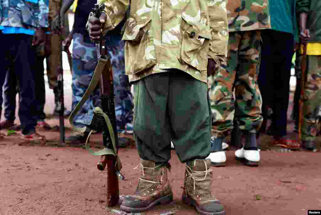 A former child soldier holds a gun while taking part in a child soldiers' release ceremony, outside Yambio, South Sudan.