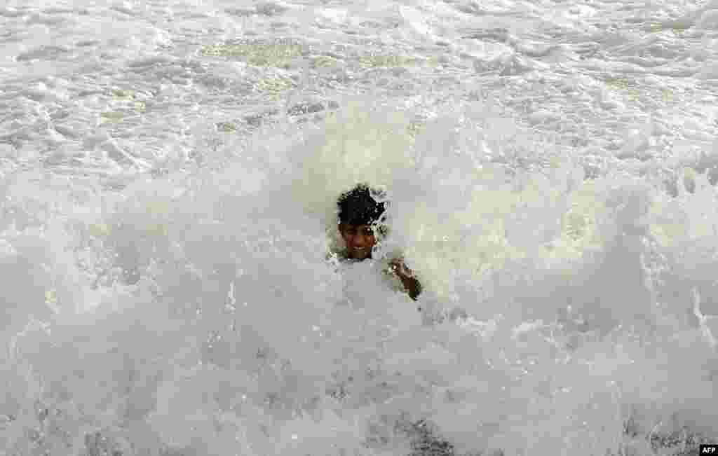 پسر سریلانکايی در ساحل دریا در کلمبو آب تنی میکند.