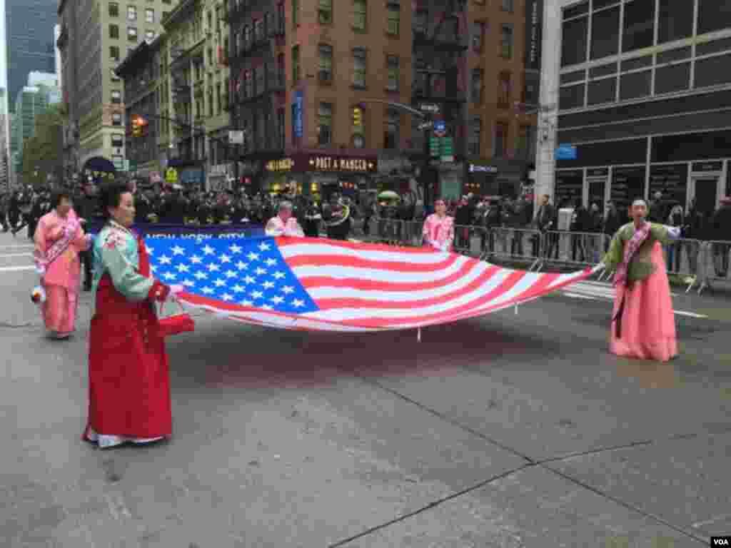 پریڈ میں شامل لوگ امریکی پرچم تھامے ہوئے