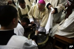 Archbishop Pierbattista Pizzaballa washes the foot of a priest during the Washing of the Feet ceremony at the Church of the Holy Sepulchre, traditionally believed by many Christians to be the site of the crucifixion and burial of Jesus Christ, in Jerusale