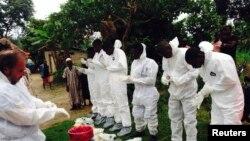 Des travailleurs bénévoles en uniforme de protection contre la maladie à virus Ebola, se préparent à enterrer une vicitme de l'épidémie qui a déjà fait 9.00 morts en Afrique de l'Ouest