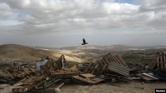 A bird flies over pieces of wood in an area near Jerusalem known as E1, where there are plans for construction of some 3,000 settler homes, December 6, 2012.