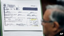 FILE- A copy of President Barack Obama's selective service card is displayed during a news conference in Phoenix, March 1, 2012, addressing the controversy surrounding his birth certificate.