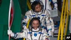 El cosmonauta ruso Mikhail Tyurin sostiene la antorcha Olímpica antes de ingresar al cohete Soyuz, acompañado por el astronauta japonés Koichi Wakata.