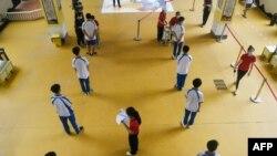 چین کے سکول میں بچے کرونا وائرس ٹیسٹ کے لیے قطار بنائے کھڑے ہیں۔