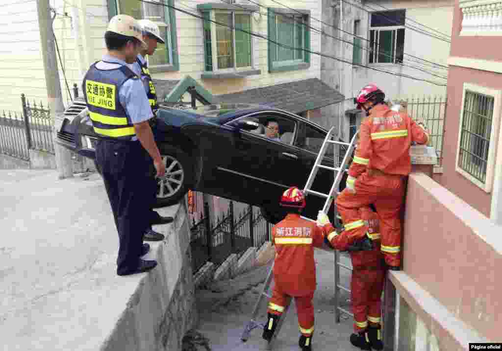 Rescue workers try to help a driver out of his car stuck over an alley in Wenzhou, Zhejiang province, Aug. 4, 2014.  The car rolled off the edge of a road after the driver was late with braking.
