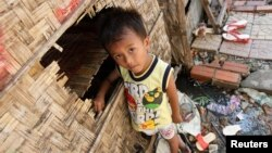 A boy plays in front of his house in Andong village, on the outskirts of Phnom Penh.
