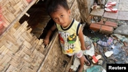 FILE - A boy plays in front of his house in Andong village, on the outskirts of Phnom Penh.