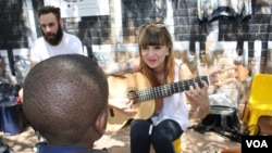 Musician Kelly Grevler gives guitar lessons to underprivileged children on a sidewalk in central Johannesburg. (D. Taylor/VOA)