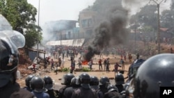 FILE- Opposition protestors clash with police in Conakry, Guinea in 2013. The Government of Guinea and two main opposition parties there have now signed an agreement.