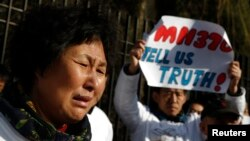 Liu Guiqiu, whose son was onboard the missing Malaysia Airlines flight MH370, cries during a gathering of family members of the missing passengers outside the Malaysian embassy in Beijing, March 8, 2015.