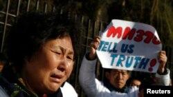 Thân nhân của một hành khách trên chuyến bay MH370 khóc bên ngoài đại sứ quán Malaysia ở Bắc Kinh, ngày 8/3/2015.