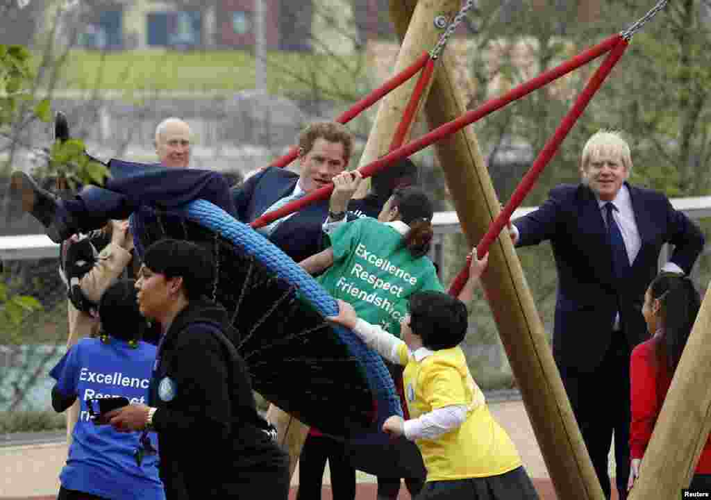 Britain's Prince Harry plays on a swing with children as Mayor of London Boris Johnson (R) looks on during a viewing of Queen Elizabeth Olympic Park ahead of its opening on April 5, 2014, at Stratford in east London.