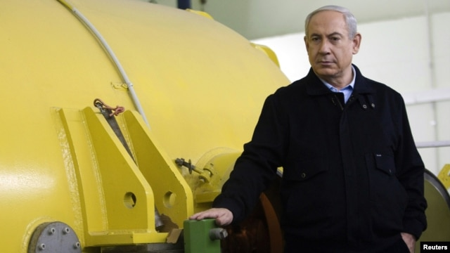 Israel's Prime Minister Benjamin Netanyahu stands next to a free-electron laser (FEL) during a visit to the Ariel University Center in the West Bank Jewish settlement of Ariel, January 8, 2013.