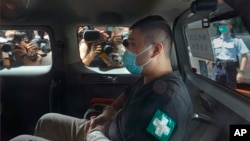 香港首位被控涉嫌違反國安法的唐英傑坐著輪椅由警車押解至法院應訊。 (2020年7月6日)