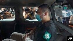 香港首位被控涉嫌違反國安法的男子唐英傑(Tong Ying-kit)坐著輪椅由警車押解至法院應訊。(2020年7月6日)