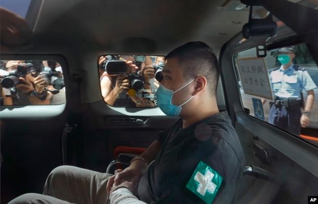 香港首位被控涉嫌违反国安法的男子唐英杰(Tong Ying-kit)坐着轮椅由警车押解至法院应讯。(2020年7月6日)