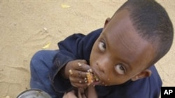 In this file photo of Thursday June 26, 2009, a Somali child eats as he is waiting to be registered at U.N. registration center in Dagahaley, Northeastern Kenya