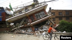 A boy riding a bicycle looks at a collapsed house after Saturday's earthquake, in Kathmandu, Nepal, April 28, 2015.