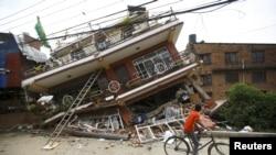 4月28日加德滿都一名男孩騎車經過因地震後倒塌的樓房前。