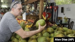 A shopper buying a coconut at a local fruit store in the Little Havana area of Miami, FL.