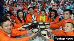 중국 건강보조제품 제조회사 중마이과기발전유한공사 소속 단체 포상관광단 4천여 명이 6일 서울 반포한강공원에서 열린 삼계탕 파티에서 삼계탕으로 건배하고 있다.