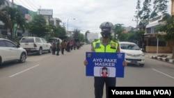 Seorang anggota Polisi membawa pesan sosialisasi agar memakai masker saat berlangsungnya operasi Yustisi yang digelar di Kota Palu, Kamis (24/09/2020) (Foto: VOA/Yoanes Litha)