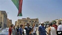 Wapiganaji waasi wakionyesha ishara ya ushindi katika wilaya ya Gorgi mjini Tripoli.