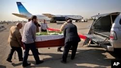 Petugas mengangkat peti jenazah seorang korban yang tewas dalam tragedi Mina di Arab Saudi, ke dalam mobil di bandar udara Mehrabad dii Teheran, Iran (3/10). (AP/Ebrahim Noroozi)