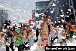 FILE - Foreign and Thai revelers dance amid foam during a foam party as part of the annual Songkran celebration, the Thai traditional New Year also known as the water festival in Bangkok, Thailand.