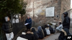 A group of college students from Israel being taught about Holocaust history at a fragment of the wall that isolated the Warsaw Ghetto and that a regional official wants to put on a list of protected historical monuments, in Warsaw, Poland, Tuesday, Feb. 20, 2018.