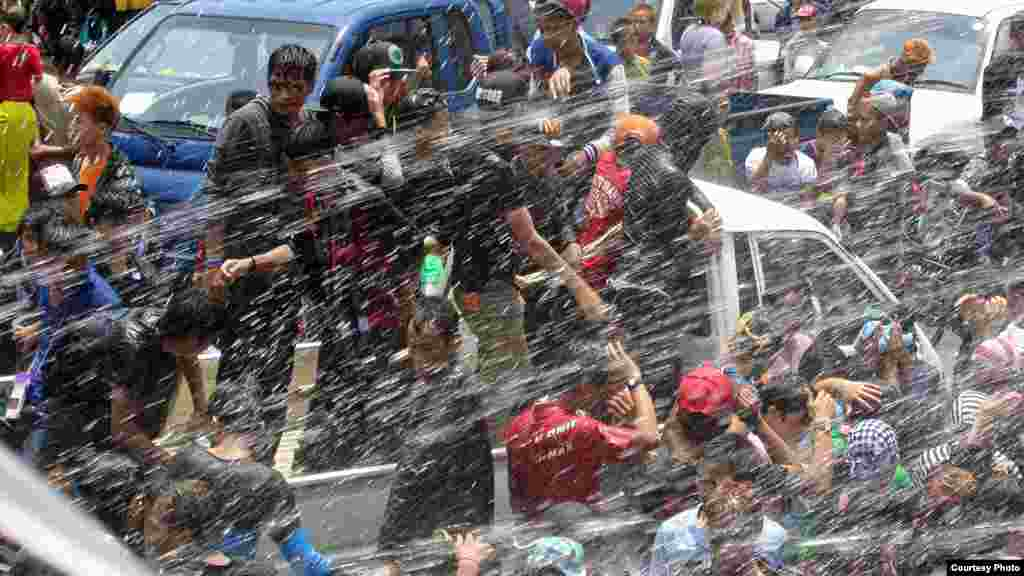 Revelers are sprayed with water during Myanmar's traditional water festival in Rangoon, Burma, April 16, 2014. (MoeMoe Htun/VOA).
