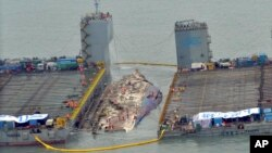 Workers prepare to lift the sunken Sewol ferry (center) in waters off Jindo, South Korea, March 23, 2017. The 6,800-ton South Korean ferry emerged from the water Thursday, nearly three years after it capsized and sank into violent seas off the country's southwestern coast.