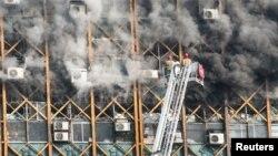 Para petugas berusaha memadamkan kebakaran yang melanda sebuah gedung tinggi di Teheran, Iran (19/1). (Reuters/Foad Ashtari)