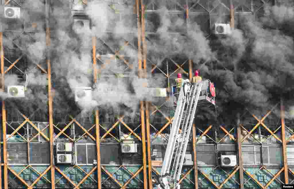 Firefighters try to put out fire in a blazing high-rise building in Tehran, Iran.
