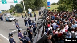 Migrants stand in front of a barrier at the border with Hungary near the village of Horgos, Serbia, Sept.15, 2015.