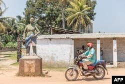 Un homme à moto passe devant le statut devant la place commémorative Zomachi à Ouidah le 4 août 2020.